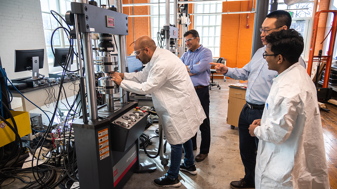 Researchers in the National Center for Additive Manufacturing Excellence are shown conducting fatigue testing.
