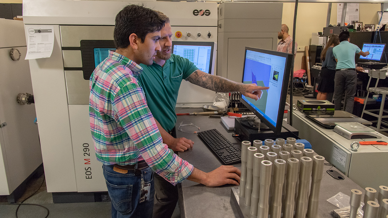Graduate student researchers Basil Paudel (left) and Jonathan Pegues work in the additive manufacturing lab in Wiggins Hall.