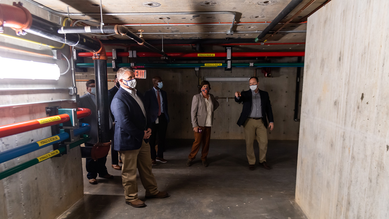 Justin Marshall (far right), director of the Advanced Structural Engineering Laboratory, shows off the facility's 4,700-cubic-foot geotechnical test chamber.