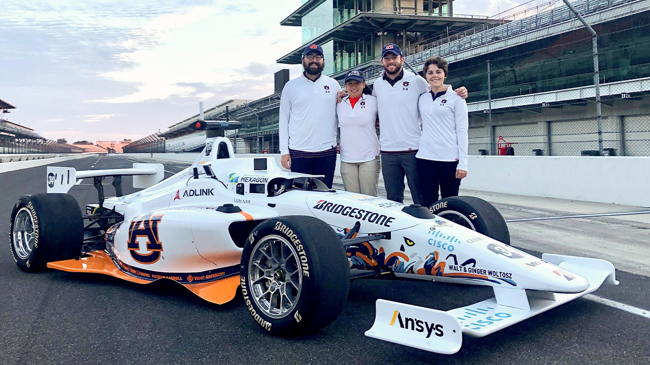 Autonomous Tiger Racing team members (from left to right) Brendan Schretter, Elizabeth Keefer, Will Bryan and Stephanie Meyer pose with their autonomous vehicle at the Indianapolis Motor Speedway. The team will compete in the first-ever Indy Autonomous Challenge on Oct. 23, 2021.