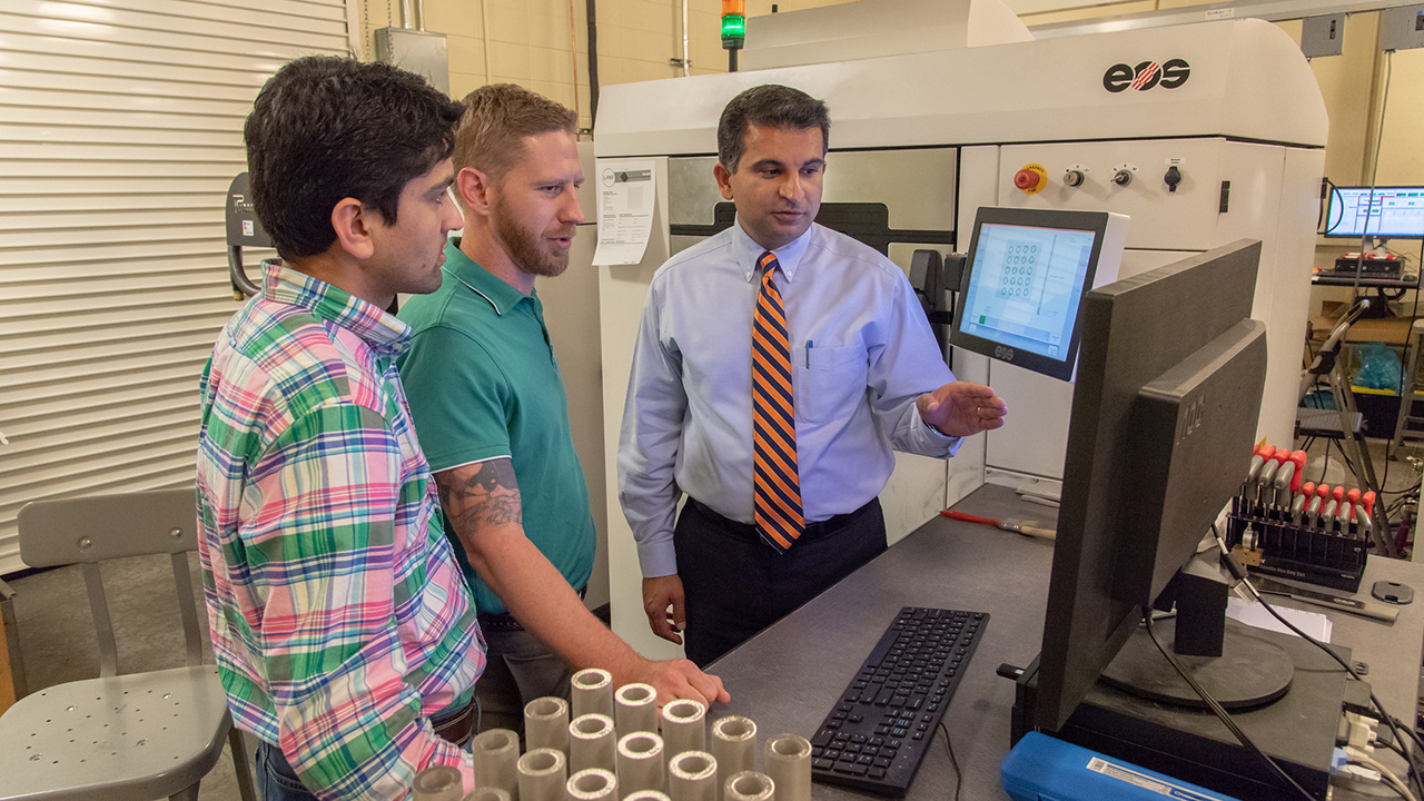 Auburn University mechanical engineering doctoral students view a 3-D model with Nima Shamsaei (right), director of the National Center for Additive Manufacturing Excellence.