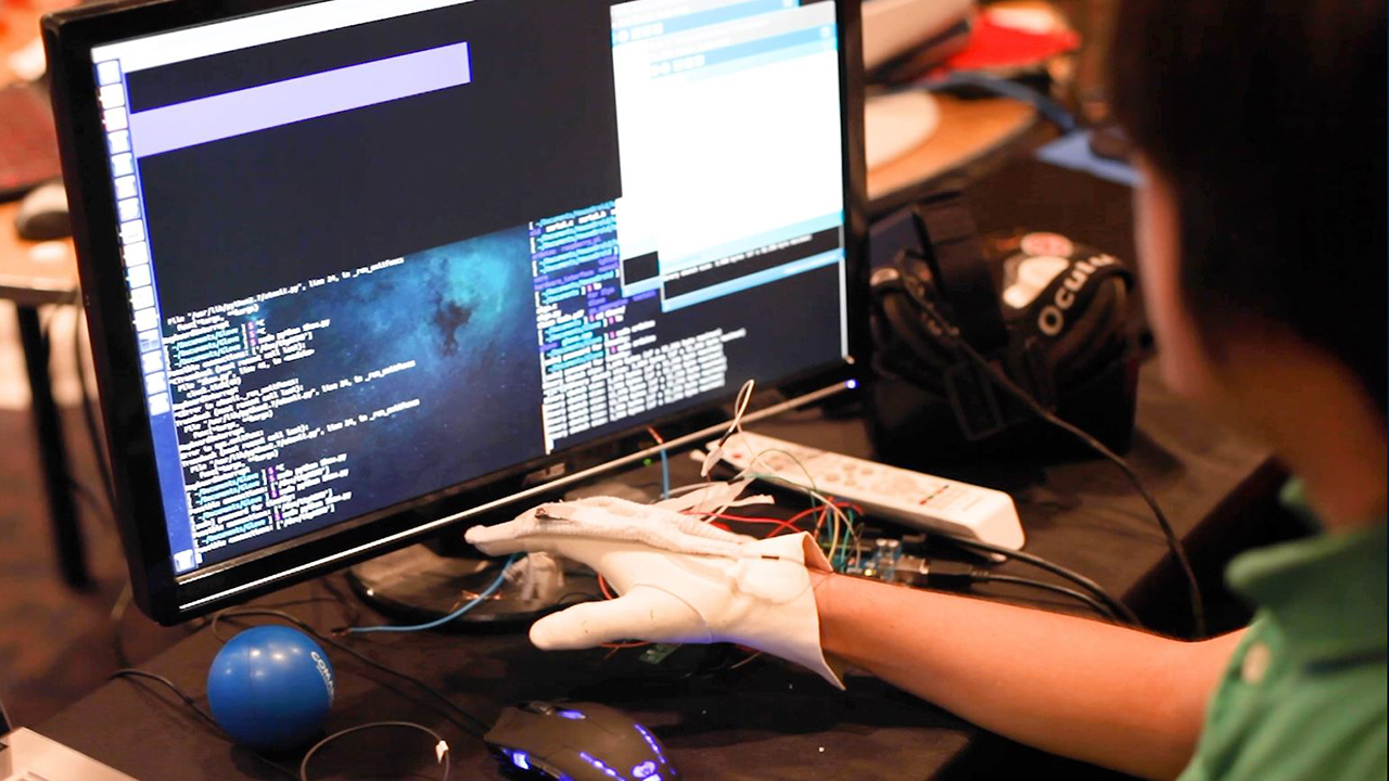 A student is seen developing a prototype at a Major League Hacking event.