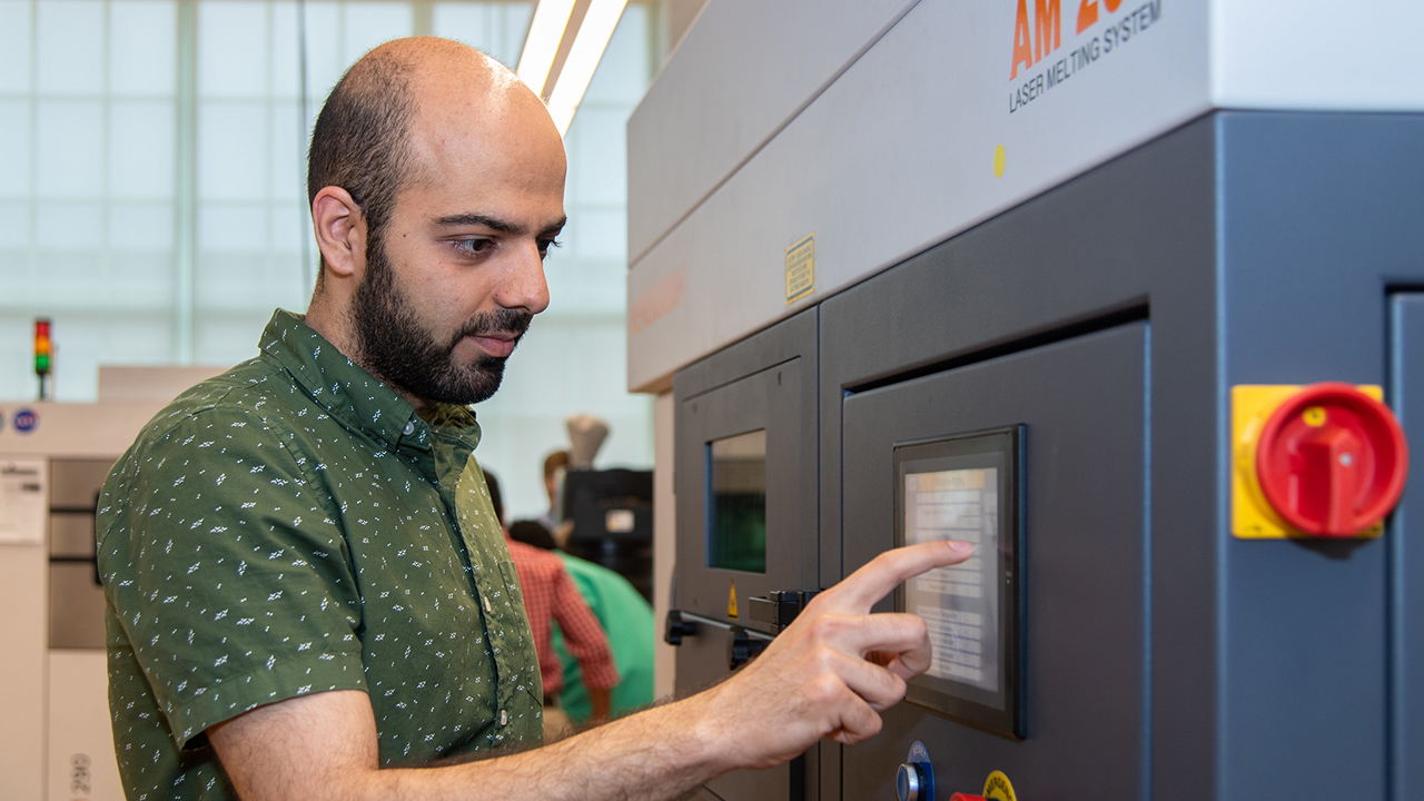 A researcher in the National Center for Additive Manufacturing Excellence is pictured operating an additive manufacturing machine.