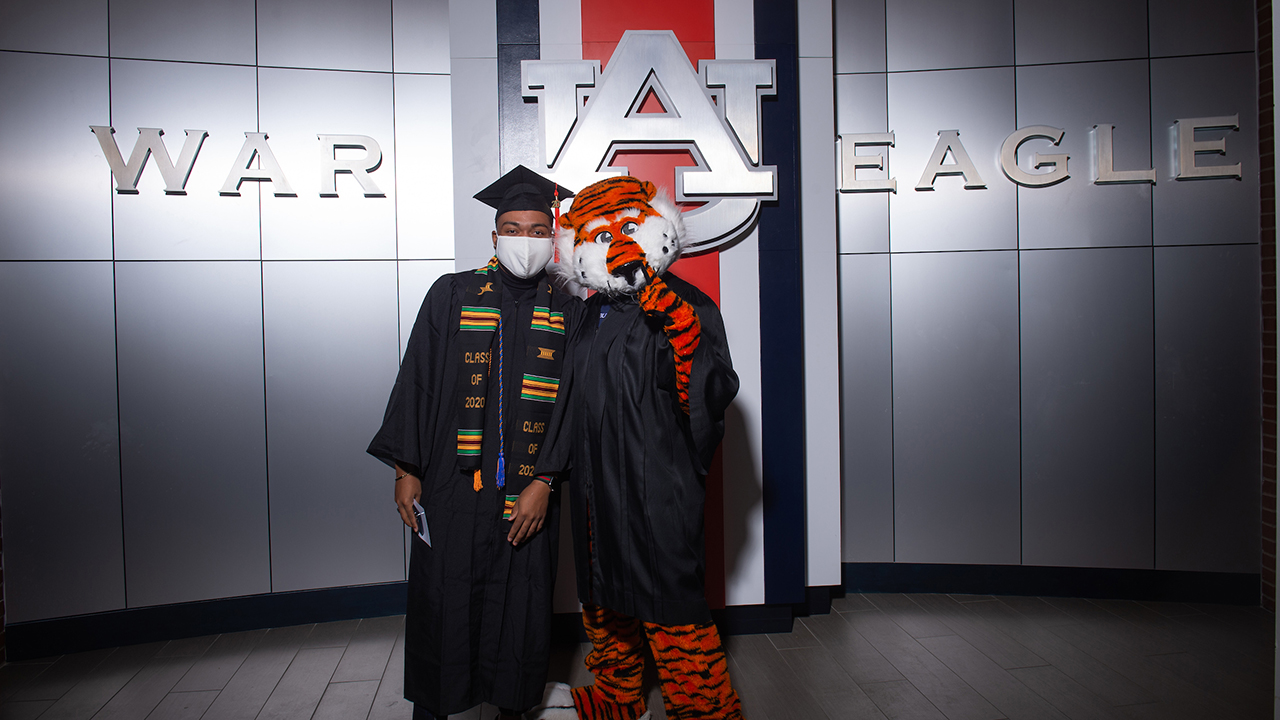 An engineering graduate is pictured with Aubie at the fall 2020 commencement ceremony.