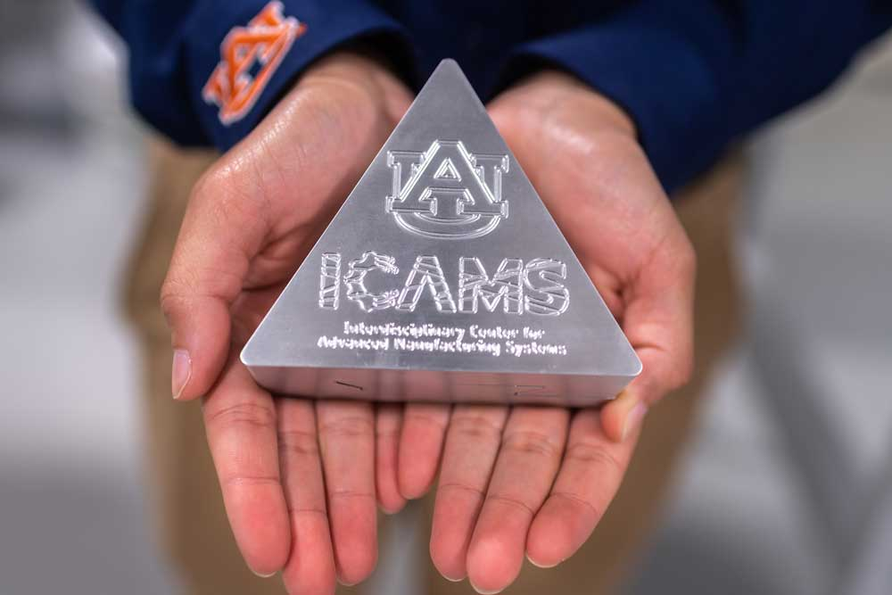 Hands holding a triangular object inscribed with the icams logo.