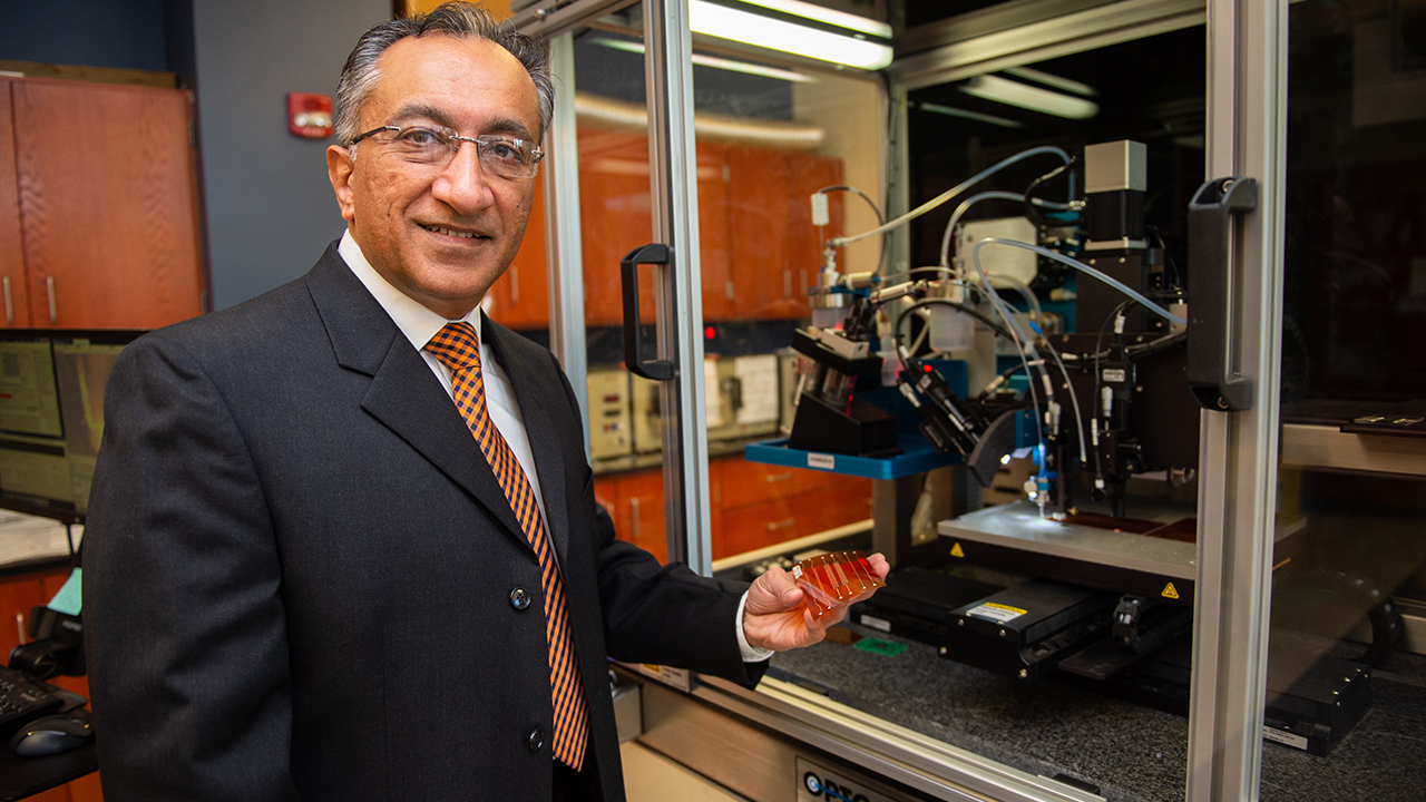 Pradeep Lall, John and Anne MacFarlane Professor of mechanical engineering, displays an additive printed flexible circuit in front of the Optomec Aerosol Jet 300 Printer.