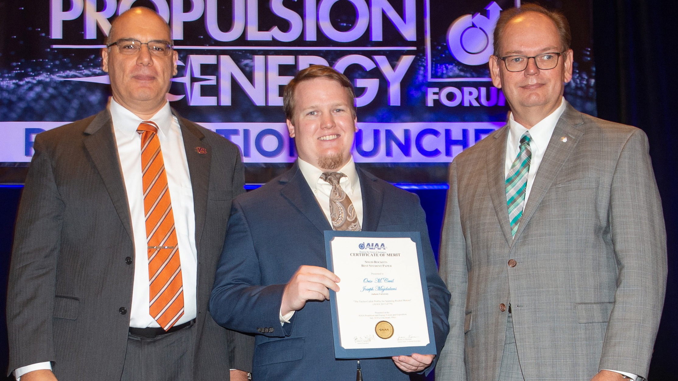 Professor Joe Majdalani and AE graduate student Orie Cecil receive the Solid Rockets Best Student Paper award from Propulsion Director Jeff Hamstra at the Propulsion and Energy Forum in Cincinnati.