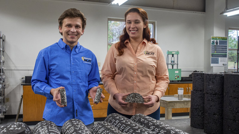 Daniel Lowell and Nicole Reed display asphalt samples in the NCAT laboratory.